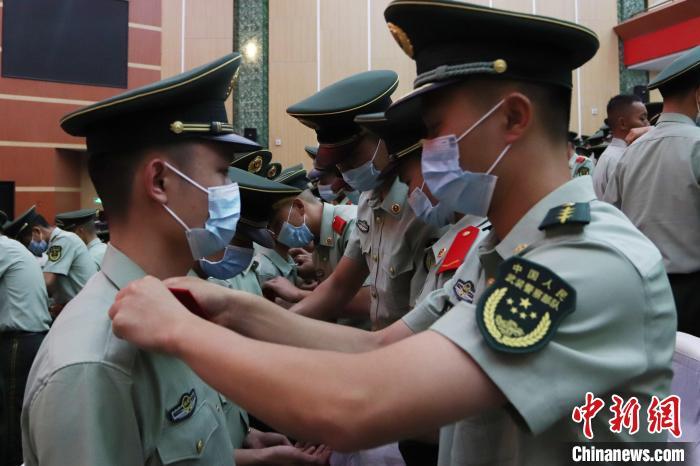 战友们为退役士兵卸下标志服饰。 黄祖万  摄