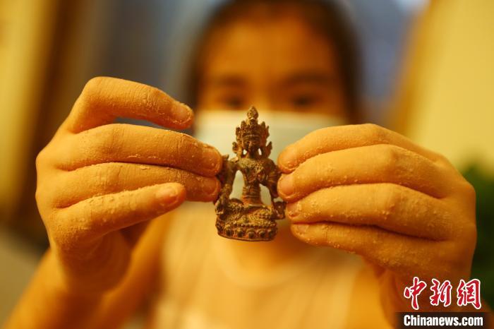 """图为一位女孩从""""考古盲盒""""中挖出的一件""""微缩文物""""。 刘占昆 摄"""