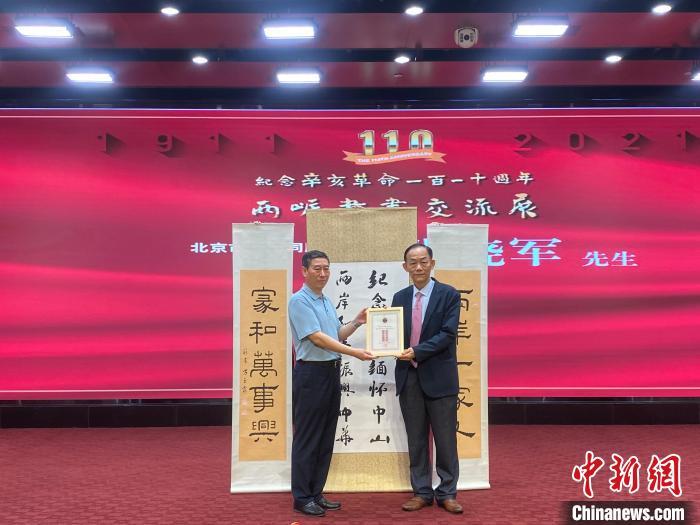 开幕式上,黄典本(右)向台湾会馆捐赠台湾书画家作品,北京市台联秘书长张晓军(左)接受捐赠?!×醮箪?摄