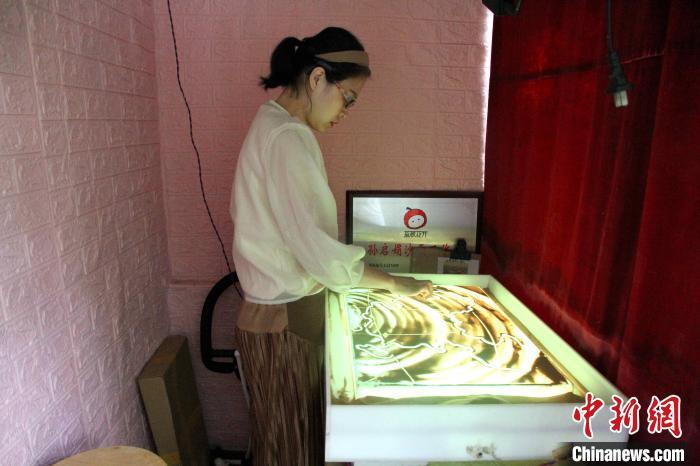 听障女画师孙启娟将阳台改造成工作室,正在练习沙画创作。 孙婷婷 摄