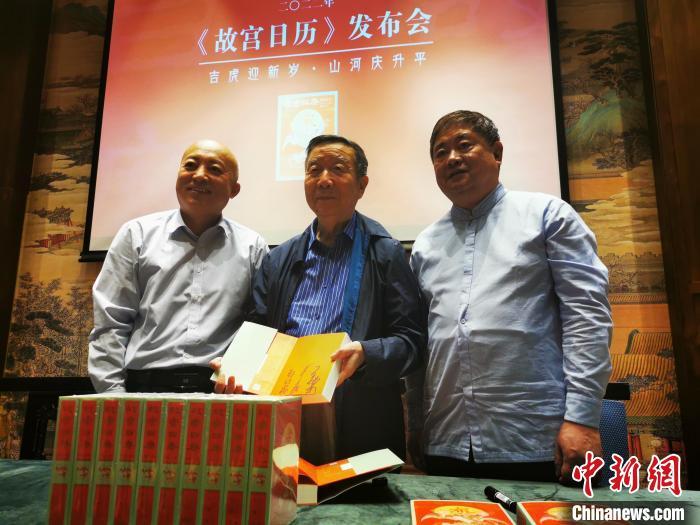 故宫博物院院长王旭东(左)与原院长郑欣淼(中)、单霁翔(右)共同为2022年《故宫日历》签名 应妮 摄