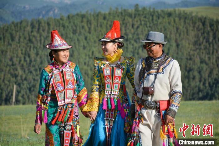 图为玛尔健(中)与阿扎阿娜(爸爸妈妈)去甘肃省张掖市肃南县康乐草原看赛马会。(资料图) 玛尔健供图