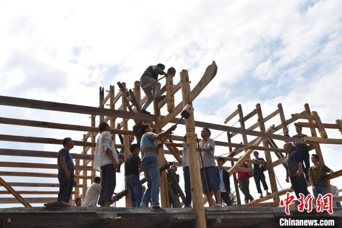 刘安喜(右三)在指挥工人进行吊脚楼架梁 廖建军 摄