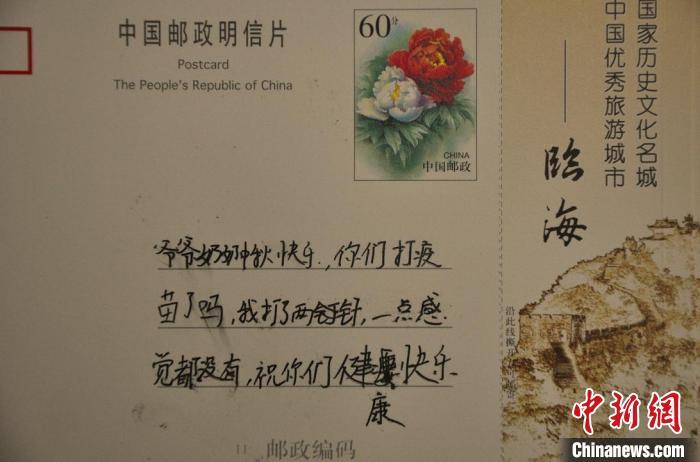誉怀小朋友在明信片上与在台湾的爷爷奶奶分享在大陆接种疫苗的感受。 张声雷 摄