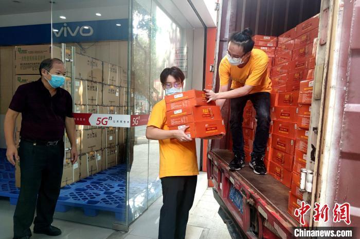 金门青年许燕宗(右)正在卸下捐赠给防疫人员的茶饮料。 吴冠标 摄
