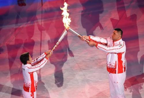图为第六棒火炬手王霜与第七棒火炬手刘玉栋传递火炬。