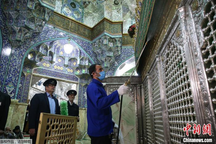 当地时间2月25日,清洁人员对伊朗库姆的清真寺进行消毒。