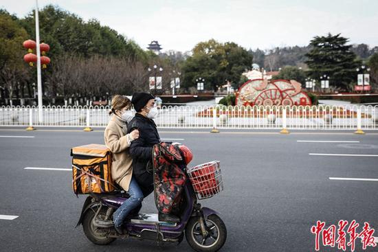2月29日,武汉市,一对年轻男女驾驶着送外卖的电动车驶过。中青报·中青网记者 赵迪/摄