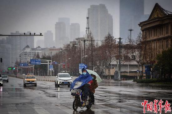 2月15日,武汉市,两位市民坐在电动车上冒雪驶过空荡荡的城市。